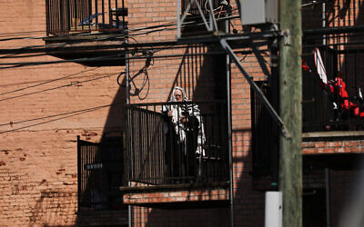 A Hasidic man prays on his balcony in a Brooklyn neighborhood on April 25, 2020 in New York City. New York City, which has been the hardest hit city in America from COVID-19, is starting to see a slowdown in hospital visits and a lowering of the daily death rate from the virus.   (Spencer Platt/Getty Images via JTA)