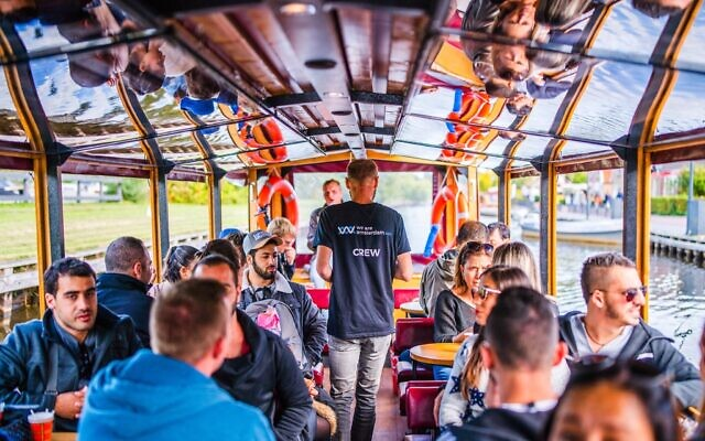 A boat belonging to the We Are Amsterdam canal tour sails in 2019. (Courtesy of We Are Amsterdam/ via JTA)
