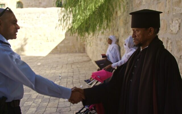 Israel police liaison officer for Christian communities Johnny Kassabri shakes hands with Fr. Zion of the Ethiopian Orthodox Church on the roof of the Church of the Holy Sepulchre. (Yoram Millo)