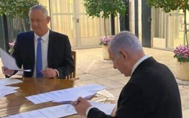Blue and White leader Benny Gantz (left) and Prime Minister Benjamin Netanyahu sign their unity government agreement on April 20, 2020. (Courtesy)