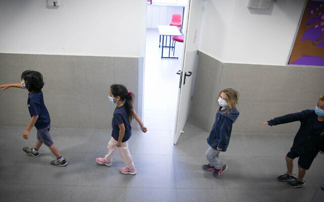 Israeli students wear protective face masks as they return to school for the first time since the outbreak of the coronavirus. (Olivier Fitoussi/Flash90)