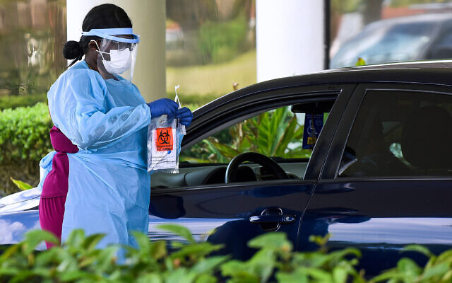 Illustrative: A health care worker conducts coronavirus nasal swabs at drive-through testing facility in Melbourne, Florida, on April 8, 2020. (Paul Hennessy/ Echoes Wire/ Barcroft Media via Getty Images/ via JTA)