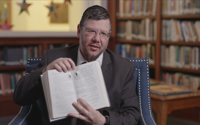 """In 'Viral: Antisemitism in Four Mutations,' Rabbi Elisar Admon shows the hole where a bullet pierced his prayer book during the Tree of Life synagogue shooting in Pittsburgh. """"It went right through the word for God,"""" he said. (PBS via JTA)"""