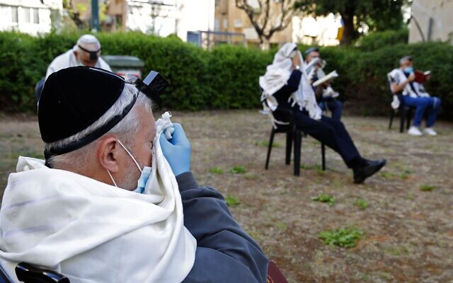 Jewish men pray while social distancing outside a closed synagogue in the coastal city of Netanya, April 23, 2020. (Jack Guez/AFP via Getty Images via JTA)