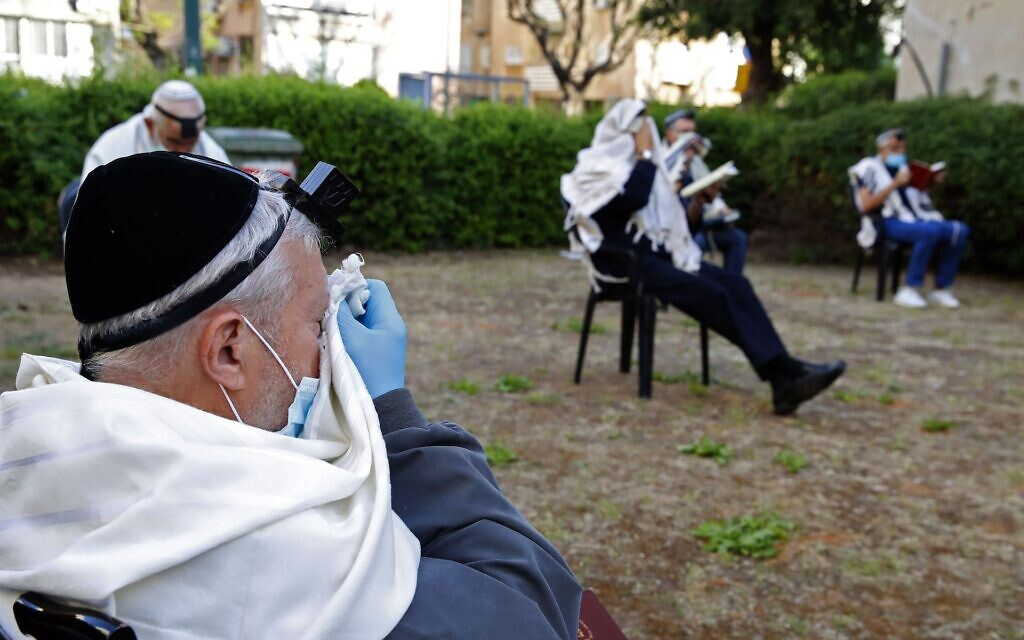 Illustrative: Religious Jewish men pray while keeping a distance from each other outside their closed synagogue in Netanya on April 23, 2020. (Jack Guez/AFP)