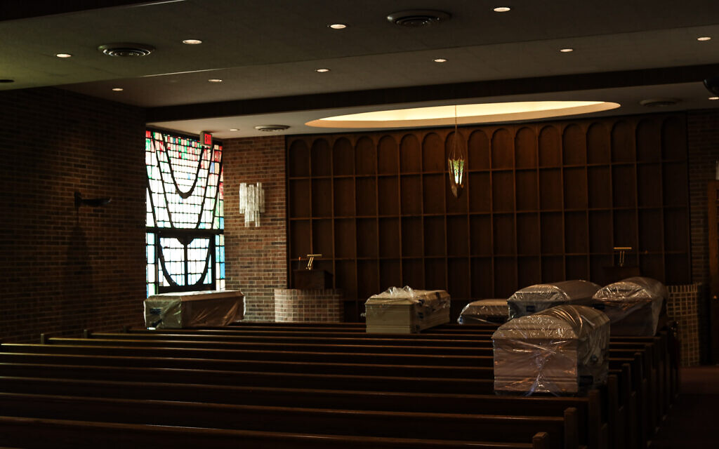 Dead from COVID-19 are waiting to be buried. The coffins are placed inside the main chapel at Gutterman's Funeral Home before being brought to their individual final burial site at a cemetery, May 15, 2020, Woodbury, New York. (Photo by Jonathan Alpeyrie/Polaris Images)