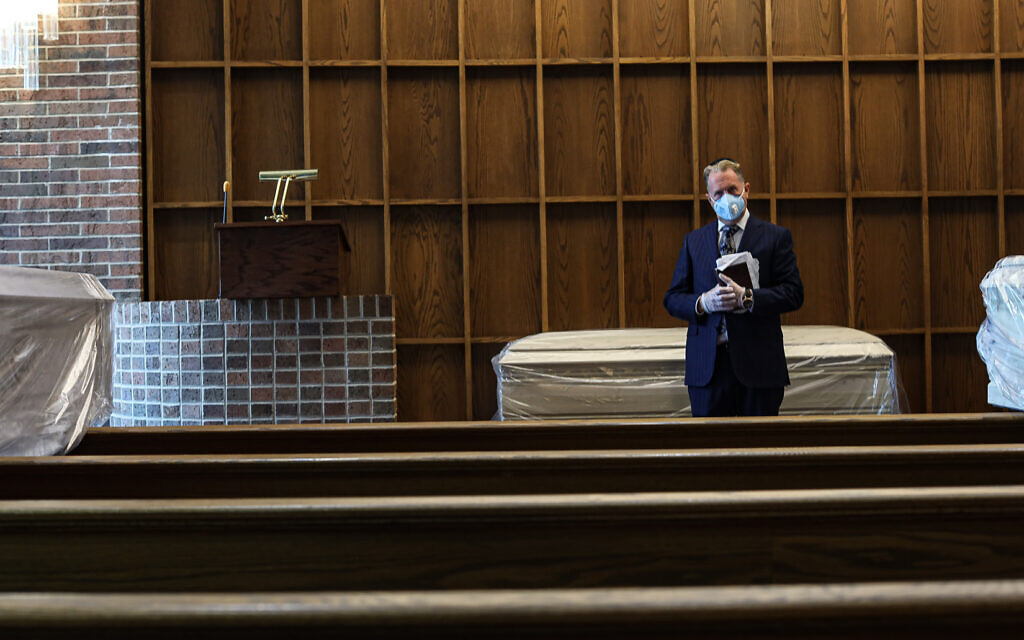 Rabbi Greg Ackerman stands next to a deceased in the chapel of Gutterman's Funeral Home, May 15, 2020, Woodbury, New York. (Photo by Jonathan Alpeyrie/Polaris Images)