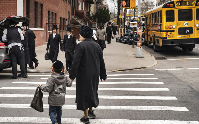 Illustrative: Pedestrians walk near the Yeshiva Kehilath Yakov School in the South Williamsburg neighborhood, April 9, 2019, in the Brooklyn borough of New York City. (Drew Angerer/Getty Images)
