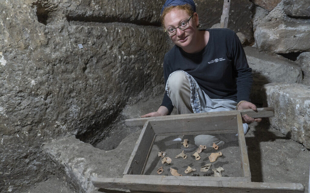 Excavation co-director Tehila Saldiel showing some of the artifacts from the excavations under Beit Straus in Jerusalem's Old City, near the Western Wall, May 2020. (Shai HaLevi/Israel Antiquities Authority)
