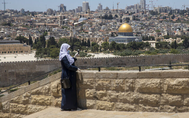 A Muslim woman wears a mask and gloves in East Jerusalem's Mount of Olives, overlooking the Dome of the Rock and al-Aqsa mosque compound on the Temple Mount, which remains shut to prevent the spread of coronavirus during the holy month of Ramadan, Friday, May 1, 2020. (AP Photo/Ariel Schalit)