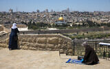 A Muslim woman prays in East Jerusalem's Mount of Olives, overlooking the Dome of the Rock and al-Aqsa mosque compound on the Temple Mount, which remains shut to prevent the spread of coronavirus during the holy month of Ramadan, May 1, 2020. (AP Photo/Ariel Schalit)