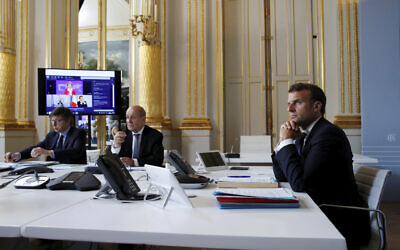 French President Emmanuel Macron, right, listens as he attends with French Foreign Minister Jean-Yves le Drian, center, an international videoconference on vaccination at the Elysee Palace in Paris, May 4, 2020. (Gonzalo Fuentes/Pool via AP)