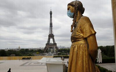 A statue wears a mask along Trocadero square close to the Eiffel Tower in Paris, May 4, 2020. (AP Photo/Christophe Ena, FILE)