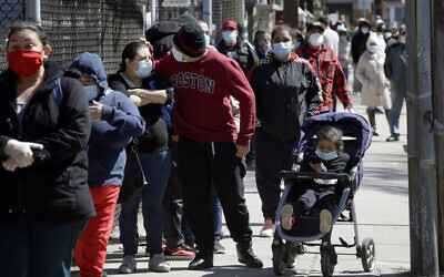People wear masks out of concern for the coronavirus while standing in line outside a Salvation Army food pantry, May 5, 2020, in Chelsea, Massachusetts. (AP Photo/Steven Senne)