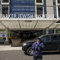 A security guard stands in the drive at the Parker Jewish Institute for Healthcare and Rehabilitation, Monday, May 4, 2020, in the Queens borough of New York. New York state is reporting more than 1,700 previously undisclosed deaths at nursing homes and adult care facilities as the state faces scrutiny over how it's protected vulnerable residents during the coronavirus pandemic. Parker Jewish Institute reported the highest number of deaths: 71.(AP Photo/Marshall Ritzel)