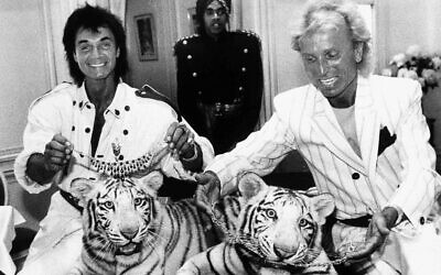 In this June 4, 1987, file photo, Las Vegas magicians Roy Horn, left, and Siegfried Fischbacher pose in New York, with their rare white tigers, Neva, left, a female, and Vegas, a male. Horn, one half of the longtime Las Vegas illusionist duo Siegfried & Roy, died of complications from the coronavirus, Friday, May 8, 2020. He was 75. (AP Photo/Scott McKiernan)