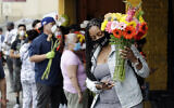Customers line up to by flowers on Mother's Day at the Los Angeles Flower Market, Sunday, May 10, 2020, in Los Angeles. Families in the U.S. and elsewhere marked Mother's Day in a time of social distancing and isolation due to the coronavirus pandemic. (AP Photo/Marcio Jose Sanchez)