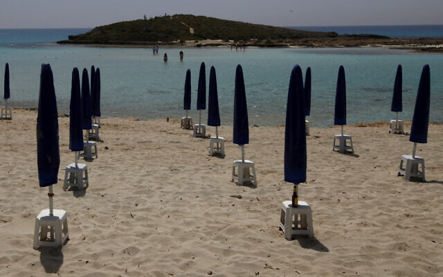 Rows of closed parasols on a nearly empty stretch of Nissi beach with a few beachgoers in the distance in Cyprus seaside resort of Ayia Napa, May 13 2020. (Petros Karadjias/AP)