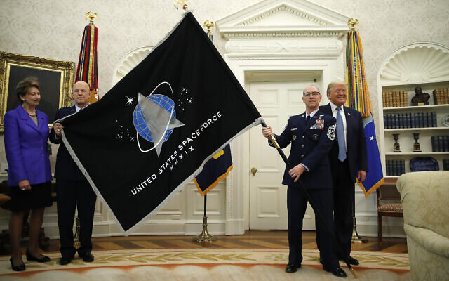 US President Donald Trump stands as Chief of Space Operations at US Space Force Gen. John Raymond, second from left, and Chief Master Sgt. Roger Towberman, second from right, hold the United States Space Force flag as it is presented in the Oval Office of the White House, May 15, 2020, in Washington.  Secretary of the Air Force Barbara Barrett stands far left. (AP Photo/Alex Brandon)