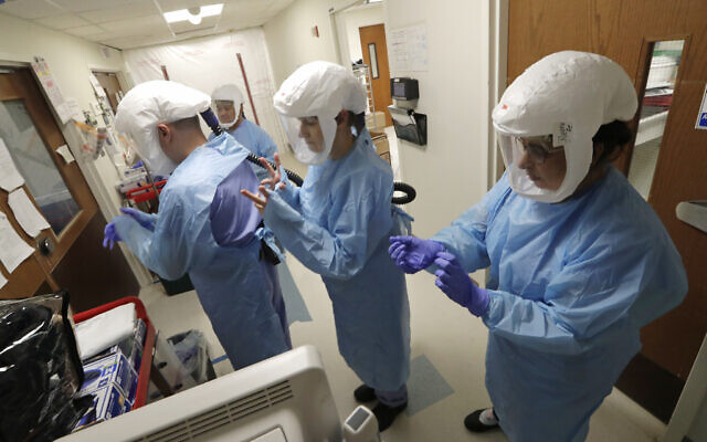 In this May 8, 2020, file photo, a team of medical workers wearing respirators and protective gear ready to enter the room of a patient in the COVID-19 Intensive Care Unit at Harborview Medical Center, in Seattle. (AP/Elaine Thompson, File)
