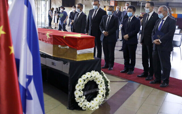 Chinese and Israeli officials pay their respect in front of the flag-draped coffin of Chinese Ambassador Du Wei, who died at his home in the coastal city of Herzliya, during a ceremony at Ben-Gurion International Airport, near Tel Aviv, Wednesday, May 20, 2020. China sent a team to Israel to repatriate the body of its ambassador. (Photo by Jack Guez/Pool via AP)