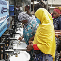 In this photo taken Monday, May 18, 2020, people use a hand-washing station installed for members of the public entering a market in Dodoma, Tanzania.  (AP Photo)