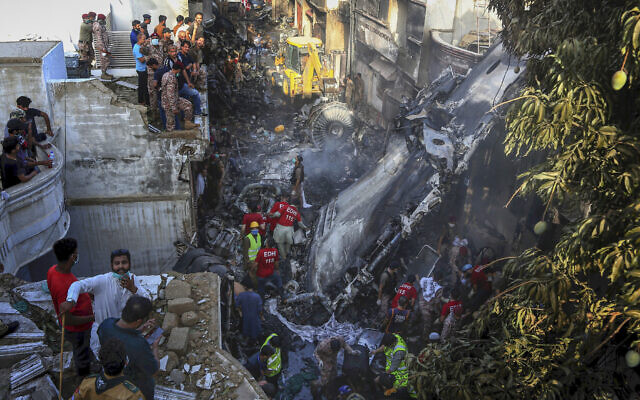 Volunteers look for survivors of a plane that crashed in a residential area of Karachi, Pakistan, May 22, 2020. (AP Photo/Fareed Khan)