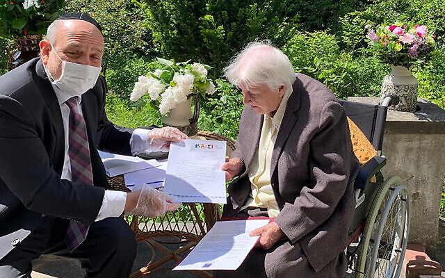 Poland's chief rabbi, Michael Schudrich, delivers letters with birthday greetings from the Israeli and Polish presidents, to Anna Kozminska, a 101-year-old Polish woman who is believed to the be oldest living person recognized by Yad Vashem for rescuing Jews during the Holocaust, in Warsaw, Poland, on Friday, May 22, 2020.  (Grazyna Pawlak via AP)