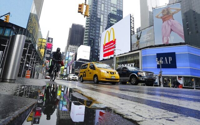 Cars and cyclists move through Times Square after a rain shower during the coronavirus pandemic, May 23, 2020, in New York. (AP Photo/Frank Franklin II)