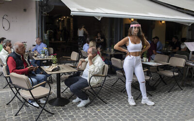 A cafe-restaurant worker stands outside as people drink coffee in Monastiraki district of Athens, May 25, 2020. (AP Photo/Petros Giannakouris)