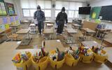 Workers disinfect as a precaution against the new coronavirus ahead of school reopening in a class at an elementary school in Gwangju, South Korea, May 26, 2020. (Park Chul-hong/Yonhap via AP)