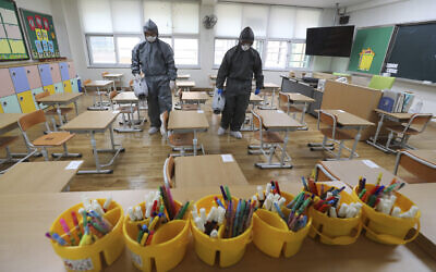 Workers disinfect as a precaution against the new coronavirus ahead of school reopening in a class at an elementary school in Gwangju, South Korea, May 26, 2020. (Park Chul-hong/Yonhap via AP)