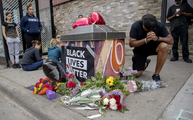People gather and pray around a makeshift memorial, May 26, 2020, in Minneapolis, near the site where a black man, who was taken into police custody the day before, later died. (Elizabeth Flores/Star Tribune via AP)