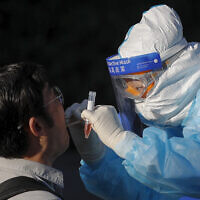 A medical worker takes a swab from a foreign reporter who was selected to cover the closing session of the Chinese People's Political Consultative Conference (CPPCC) for the coronavirus test, at a hotel in Beijing, May 27, 2020. (Andy Wong/AP)
