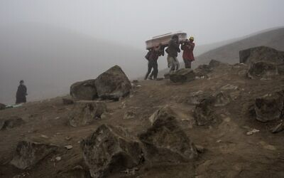 Cemetery workers carry the coffin with the corpse of Flavio Juárez, 50, who died from COVID-19, at the Nueva Esperanza cemetery on the outskirts of Lima, Peru, May 26, 2020. (Rodrigo Abd/AP)