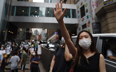 A protester gestures with five fingers, signifying the 'Five demands - not one less' during a protest in Central Government Complex in Hong Kong, May 27, 2020. (AP Photo/Kin Cheung)