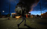 A man poses for a photo in the parking lot of an AutoZone store in flames, while protesters hold a rally for George Floyd in Minneapolis on Wednesday, May 27, 2020 (Carlos Gonzalez/Star Tribune via AP)