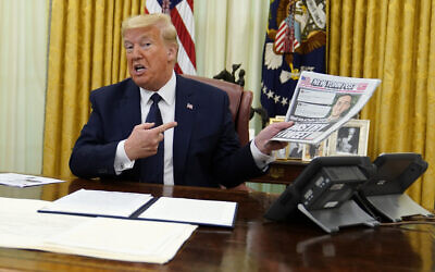 US President Donald Trump holds up a copy of the New York Post as he speaks before signing an executive order aimed at curbing protections for social media giants, in the Oval Office of the White House, Thursday, May 28, 2020, in Washington. (AP Photo/Evan Vucci)