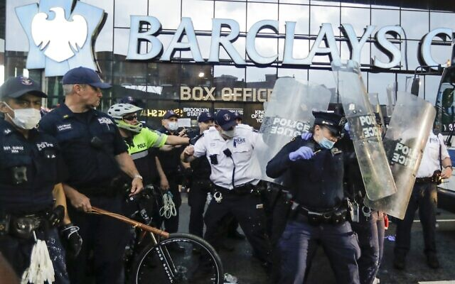 Police officers protect themselves with shields as protesters throw debris during a rally Friday, May 29, 2020, in the Brooklyn borough of New York, at the Barclays Center (AP Photo/Frank Franklin II)