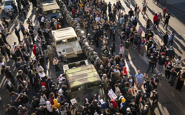 A group of US protesters surrounded several National Guard vehicles that were driving on Lake Street towards the blockade under the Hiawatha Light Rail station and forced them to reverse out in Minneapolis, Minnesota, May 29, 2020. (Renee Jones Schneider/Star Tribune via AP)