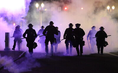 Police officers walk enveloped by teargas in Portland, Friday, March 29, 2020 (Dave Killen/The Oregonian via AP)