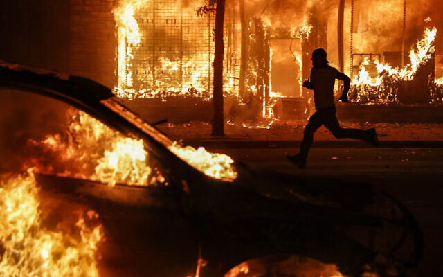 A protester runs past burning cars and buildings on Chicago Avenue, Saturday, May 30, 2020, in St. Paul, Minnesota (AP Photo/John Minchillo)