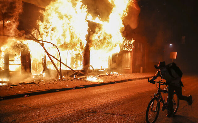 A protester rides his bike past a burning building that housed a check cashing business, Friday, May 29, 2020, in St. Paul, Minn. (AP/John Minchillo)