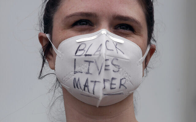 A woman wears a face mask with Black Lives Matter written on it at a protest over the Memorial Day death of George Floyd, a handcuffed black man in police custody in Minneapolis, in San Francisco, Saturday, May 30, 2020. (AP Photo/Jeff Chiu)