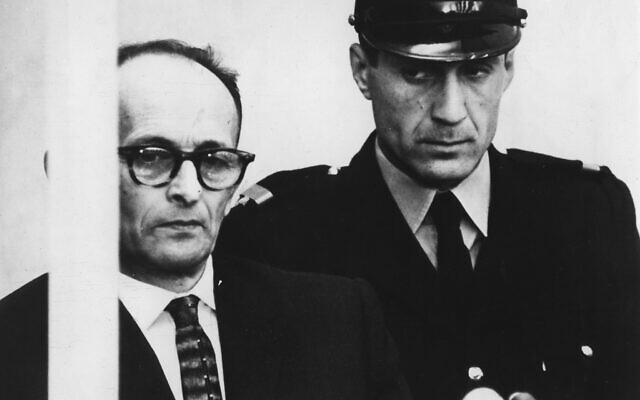 Adolf Eichmann is seen standing in his bullet proof glass box as the charges against him are read during judical proceedings in the Beit Ha'Am building in Jerusalem,  April 12, 1961. (AP Photo/Str)