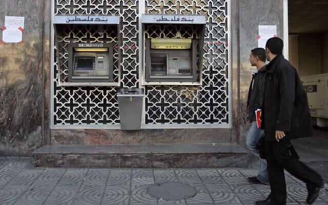 File: Palestinian pass by a cash machine of the Bank of Palestine branch in Gaza City, Thursday, Dec. 4, 2008 (AP Photo/Hatem Moussa)