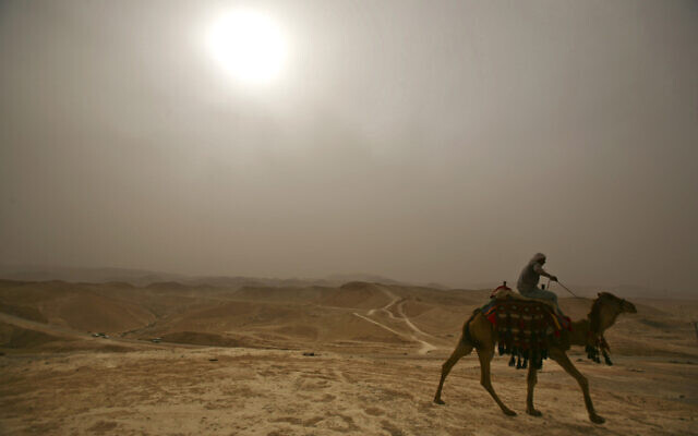 A Palestinian rides his camel in the haze next to Nebi Musa Mosque, not seen, near the West Bank town of Jericho during a heat wave on May 4, 2009. (AP Photo/Dan Balilty)