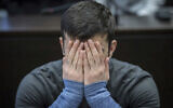 22-year-old Ali Bashar covers his face as he arrives at a court in Wiesbaden, Germany, March 12, 2019. (Boris Roessler/dpa via AP, Pool)
