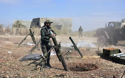 Illustrative: Syrian army soldiers prepare to launch a mortar towards insurgents in the village of Kfar Nabuda, in the countryside of Hama province on May 11, 2019. (SANA via AP)