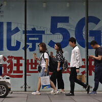 People walk toward a police robot mounted with surveillance cameras patrol past a 5G network advertisement at a shopping district in Beijing, Wednesday, May 15, 2019. (AP/Andy Wong)